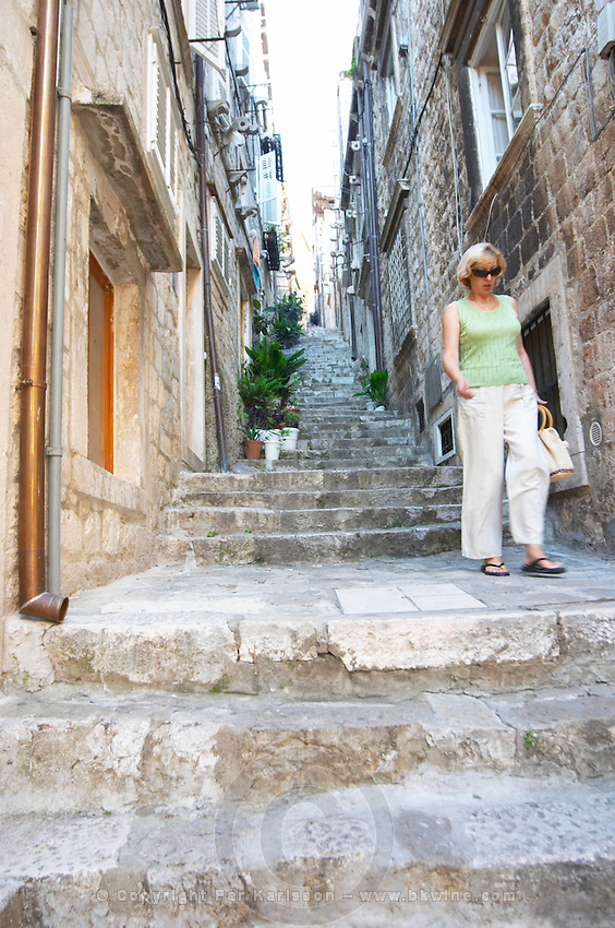 View from the Prijeko street up a narrow street with steep stairs. Narrow cobble stone street, a woman walking down the steps. Dubrovnik, old city. Dalmatian Coast, Croatia, Europe.