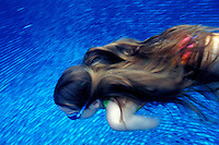 A young girl with flowing waist length hair and wearing goggles swims underwater in a blue tiled pool.