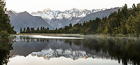 Winter dawn reflections of Mount Tasman and  Aoraki, Mount Cook of Southern Alps in Lake Matheson, Westland Tai Poutini National Park, West Coast, UNESCO World Heritage Area, South Westland, New Zealand, NZ