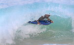 A man makes it under a curling wave at  Sandy Beach in Hawaii.