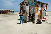 A Haitian family in front of a shack in the slum of Cité Soleil, Port-au-Prince, Haiti, 11 July 2008. Cité Soleil is considered one of the worst slums in the Americas, most of its 300.000 residents live in extreme poverty. Children and single mothers predominate in the population. Social and living conditions in the slum are a human tragedy. There is no running water, no sewers and no electricity. Public services virtually do not exist - there are no stores, no hospitals or schools, no urban infrastructure. In spite of this fact, a rent must be payed even in all shacks made from rusty metal sheets. Infectious diseases are widely spread as garbage disposal does not exist in Cité Soleil. Violence is common, armed gangs operate throughout the slum.