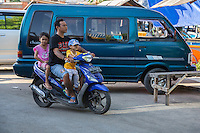 Jimbaran, Bali, Indonesia.  Father and Children on Motorbike, no Helmets.