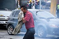 CALARCA - COLOMBIA, 30-04-2021: Un transeunte trata de huir de los gases lacrimogenos en la población de Calarcá a la salida de la vía que conduce al alto de La Línea durante el tercer día de Paro Nacional en Colombia hoy, 30 abril de 2021, y que comenzó el pasado 28 de abril de 2021 para protestar por la reforma tributaria que adelanta el gobierno de Ivan Duque además de la precaria situación social y económica que vive Colombia. El paro fue convocado por sindicatos, organizaciones sociales, estudiantes y la oposición. / A passerby tries to escape the tear gas in the town of Calarcá at the exit of the road that leads to the top of La Línea during the third day of the National Strike in Colombia today, April 30, 2021, and which began on April 28, 2021 to protest the tax reform that the government of Ivan Duque is also advancing of the precarious social and economic situation that Colombia is experiencing. The strike was called by unions, social organizations, students and the opposition in Colombia. Photo: VizzorImage / Santiago Castro / Cont