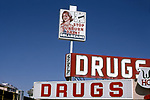 Drug store with clock sign advertsing Solarcaine for sunburn pain.