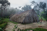 Nawade Caiga walks out of a traditional Waorani (Huaroni) palm leaf house in the tiny community of Cononaco Chico where there are only three houses and only one is inhabited.