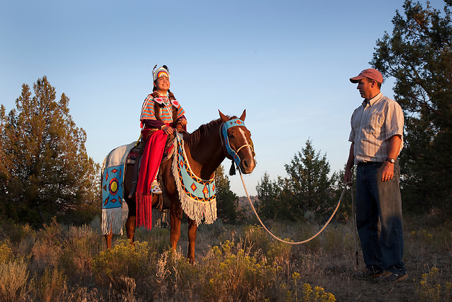 Native American family of two sisters dressed in traditional clothing and beadwork horseback ride the family's decorated horse while their father holds onto the lead line to ensure both daughters safety, Warm Springs Indian Reservation, Oregon.