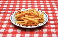 Un piatto di patatine fritte fatte in casa su tovaglia a quadretti bianchi e rossi --- A dish of home made french fries on a red and white checkered tablecloth