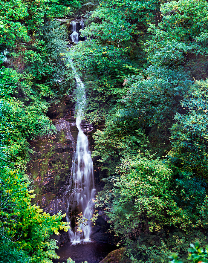 Black Spout Waterfall descends from high up on the Edradour Burn.  A circular path in the Black Spout Wood just on the edge of the town of Pitlochry, Scotland provides for a pleasant hike.