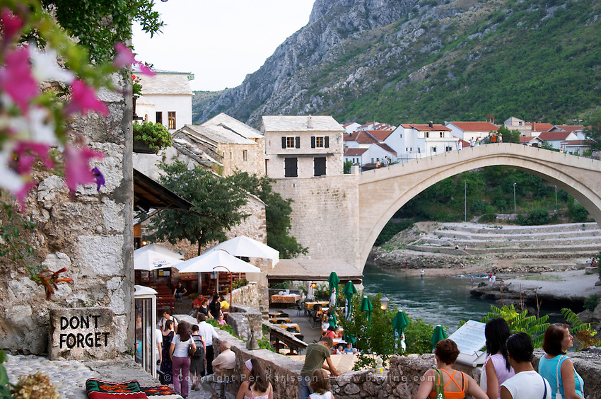 View along the river of the old reconstructed bridge. The busy old market bazaar street Kujundziluk with lots of tourist craft and art shops and street merchants. A sign saying 'don't forget' Historic town of Mostar. Federation Bosne i Hercegovine. Bosnia Herzegovina, Europe.