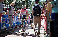 'maglia rosa' Simon Gerrans (AUS/Orica-GreenEDGE) coming back from the start podium in Albenga<br /> <br /> 2015 Giro<br /> stage 2: Albenga - Genova (177km)