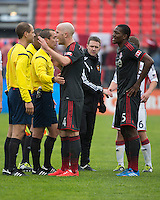 Toronto, Ontario - May 3, 2014: Toronto FC midfielder Michael Bradley #4 and Toronto FC defender Doneil Henry #15 talk with the officials after the final whistle during a game between the New England Revolution and Toronto FC at BMO Field.<br /> The New England Revolution won 2-1.