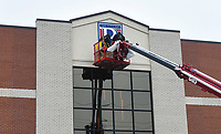 """Sign installers Nate Frihart (from left) and Austin Yates install a sign, Thursday, February 11, 2021 at the Bentonville Administrative Services building in Bentonville. A crew from Arkansas Sign and Banner installed the big """"B"""" on the City of Bentonville Administrative Services building. Check out nwaonline.com/210212Daily/ for today's photo gallery. <br /> (NWA Democrat-Gazette/Charlie Kaijo)"""