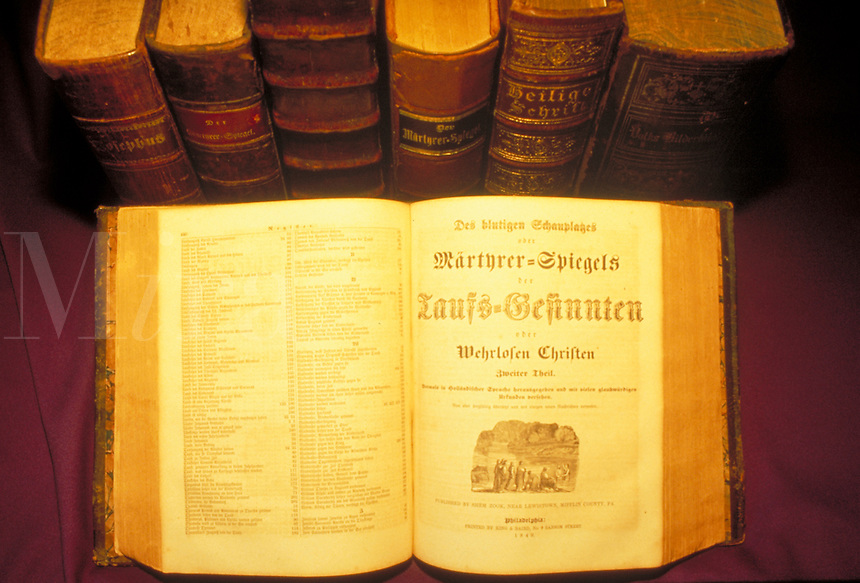The Martyrs Mirror, German language edition, is shown with other historic religious books of Amish and Mennonite Christian experience including accounts of persecution and martyrdom. Lancaster Pennsylvania United States Amish library.