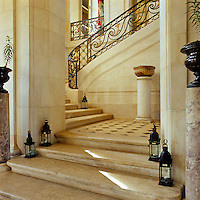 The grand marble staircase with its black and gold wrought iron banisters is lit by simple black metal garden lanterns