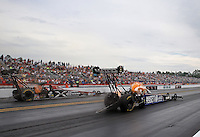 Mar. 17, 2013; Gainesville, FL, USA; NHRA top fuel dragster driver Antron Brown (right) races alongside Spencer Massey during the Gatornationals at Auto-Plus Raceway at Gainesville. Mandatory Credit: Mark J. Rebilas-