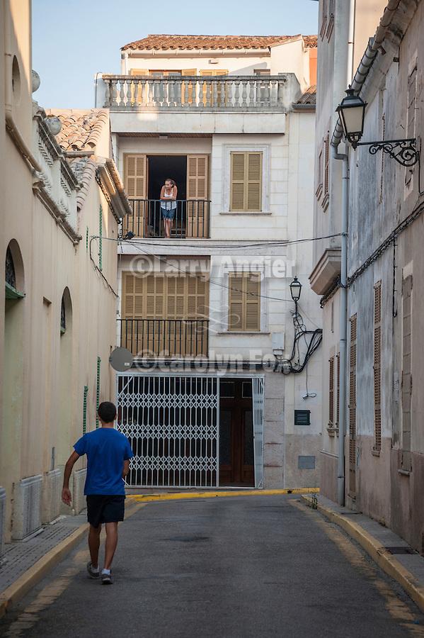 A person in blue walks a narrow street in Margalida, Mallorca