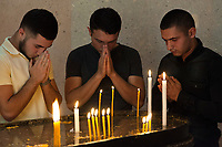 """Nagorno-Karabakh, also known as Artsakh, is a landlocked region in the South Caucasus. Stepanakert is the capital and the largest city of the Republic of Artsakh (better known as Nagorno-Karabakh). Armenian Apostolic Church. Three young men pray at """" Holy Mother of God Cathedral """", also known as Surb Astvatsamor Hovanu Cathedral. The church - under construction for 12 years - was consecrated on April 7, 2019. Nagorno-Karabakh is a disputed territory, internationally recognized as part of Azerbaijan, but most of the region is governed by the Republic of Artsakh (formerly named Nagorno-Karabakh Republic), a de facto independent state with Armenian ethnic population. Since 1994, regular peace talks between Armenia and Azerbaijan mediated by the OSCE Minsk Group have failed to result in a peace treaty.  6.10.2019 © 2019 Didier Ruef"""