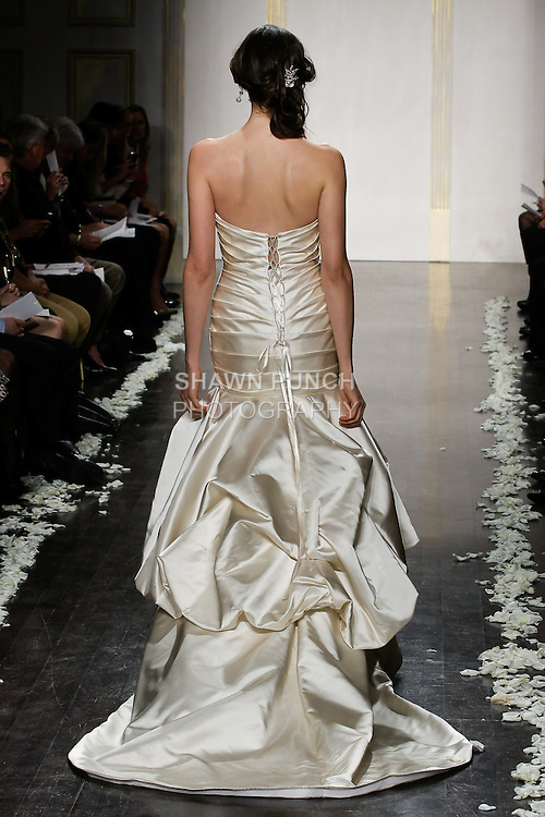 Model walks runway in an Antique satin A-line gown, gathered elongated corset bodice with strapless sweetheart neckline, pickup bubble and chapel train wedding dress, by Lazaro Perez, from the Tara Keely Spring 2012 Bridal fashion show.