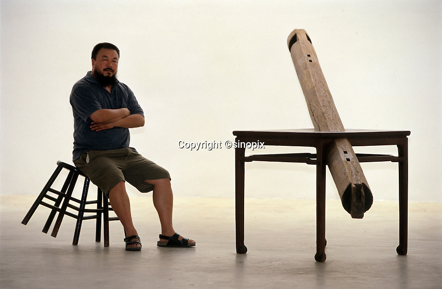 Ai Weiwei,  Chinese contemporary artist, poses with his work in his studio in Beijing, China. 2004 (photo by Lou Linwei)