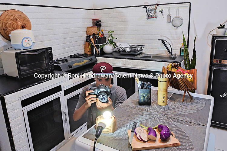 Pictured:  Roni's setup in his kitchen<br /> <br /> CAPTURED USING JUST A DESK LAMP AND A CAMERA DURING LOCKDOWN.......Amazing up close photos show fruit and vegetables as you've never seen them before.  Photographer Roni Hendrawan used a special lens to capture the vibrant images of aubergines, sweetcorn, onions, limes, cucumbers, tomatoes and peppers.<br /> <br /> The 29 year old spent three months assembling the produce in lockdown from what he would ordinarily eat before doing the shoot in his kitchen with a macro lens.  SEE OUR COPY FOR DETAILS.<br /> <br /> Please byline: Roni Hendrawan/Solent News<br /> <br /> © Roni Hendrawan/Solent News & Photo Agency<br /> UK +44 (0) 2380 458800