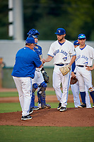 Bluefield Blue Jays starting pitcher Cre Finfrock (22) hands the ball to manager Dennis Holmberg (35) after being removed from a game against the Bristol Pirates on July 26, 2018 at Bowen Field in Bluefield, Virginia.  Bristol defeated Bluefield 7-6.  (Mike Janes/Four Seam Images)