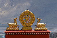 Twelve-spoked Dharmachakra or Wheel of Law with two deer, represents the Buddha's first teaching of the Middle Way in Deer Park, Sarnath, India, Drepung Monastery, Lhasa, Tibet, China..