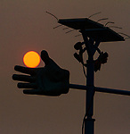 The sun obsured by smoke from the northern California forest fires was seen setting on top of a weather vane in Emeryville California.