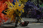 PHOTOG LAYS on GROUND to GET a BETTER SHOT of COLORFUL BALLOONS WHICH SURROUND AFRICAN SUPPORTER PARTICIPATING in GAY PRIDE PARADE<br />