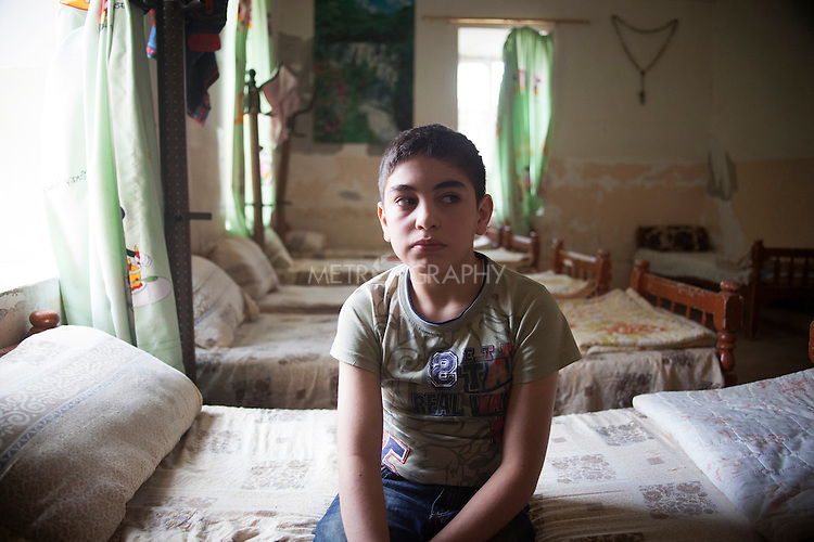 31/10/14. Alqosh, Iraq. Iraqi-Christian orphan Wassam sits on his bed in the orphanage dormitory he shares with 8 other orphans,
