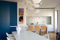A white lacquered aluminium table in the kitchen/dining area is surrounded by Eames chairs