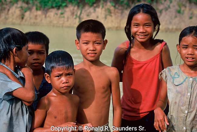 CHILDREN POSE BY RIVER IN CAMBODIA