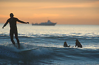 Pacific Beach, San Diego, California, USA:  Monday, January 19 2009.  Mike Russell of Pacific Beach enjoys the fine weather and good swell just off the beach at the bottom of Loring Street.  The Martin Luther King Jnr Day holiday was marked by warm weather, big surf and a technicolored sunset as much of the rest of the country shivered in the cold.