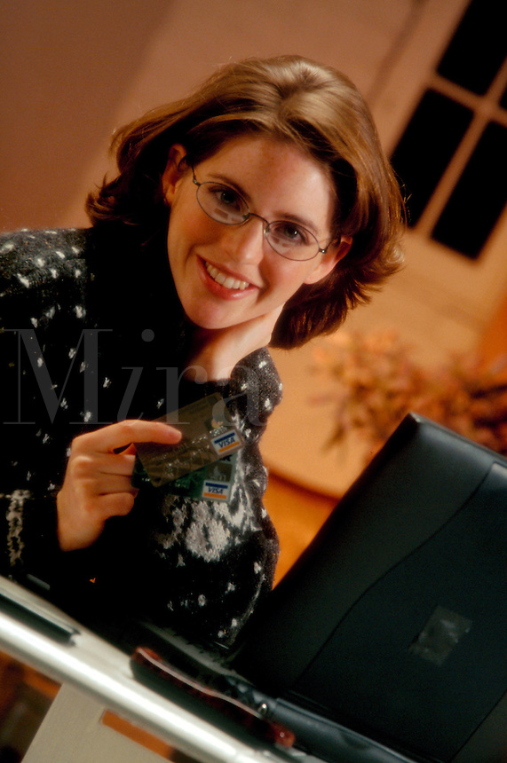 A smiling young woman in glasses working with a laptop computer.