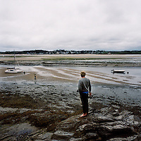 A man watches his child collect shells on the sand on the sea shore in Padstow, Cornwall.