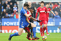 Jordan Ayew of Swansea is challenged by Harry Maguire of Leicester City during the Premier League match between Leicester City and Swansea City at the King Power Stadium, Leicester, England, UK. Saturday 03 February 2018