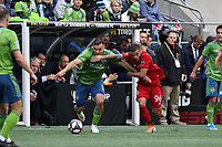 SEATTLE, WA - NOVEMBER 10: Jordan Morris #13 of the Seattle Sounders FC holds off a challenge by Auro Jr. #96 of Toronto FC during a game between Toronto FC and Seattle Sounders FC at CenturyLink Field on November 10, 2019 in Seattle, Washington.