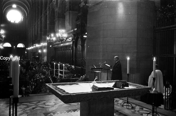 Basilique Saint-Sernin. 6 décembre 1969. Obsèques de Didier Daurat : au 1er plan autel, cierges ; au 2nd plan le pilote André Turcat (de profil) lisant l'épître derrière un pupitre ; en arrière-plan cercueil recouvert de gerbes de fleurs, foule. Observation: Didier Daurat est décédé dans la nuit du 2 au 3 décembre 1969. Il est d'abord enterré au cimetière Terre-Cabade. Puis le 21 avril 1972, son cercueil est transféré et enterré en bordure des pistes de l'aérodrome de Montaudran.