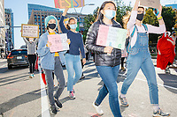 """Protestors march along Tremont Street as they make their way to Boston City Hall during the 2020 Women's March protest in opposition to the re-election of US president Donald Trump in Boston, Massachusetts, on Sat., Oct. 17, 2020.<br /> The signs here read """"Resist,"""" """"'Women belong in all places where decisions are being made' -RBG (but maybe not Amy Coney Barrett)"""" """"Resist: sexism, racism, xenophobia, homophotobia, ignorance, corruption, and hate,"""" and """"Honestly there's so much to protest / Time to be the change."""""""