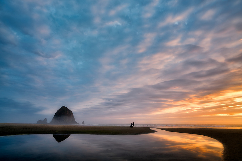 Cannon Beach at sunset with Haystack Rock, stream and couple with dog. Oregon