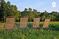 Garden chairs Empty facing green wheat field at sunset (Licence this image exclusively with Getty: http://www.gettyimages.com/detail/81867353 )