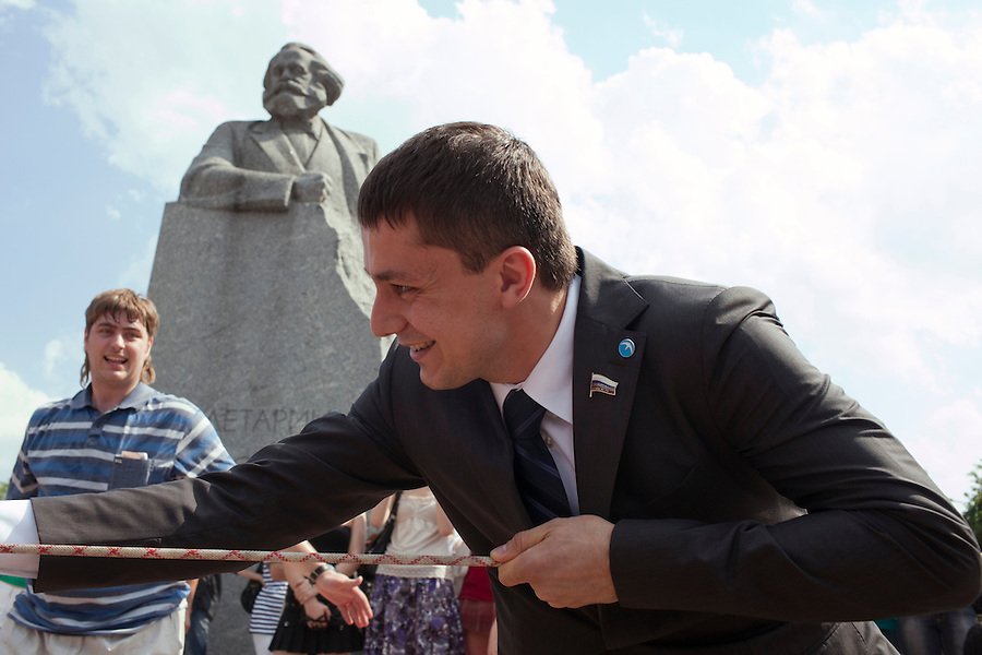Moscow, Russia, 12/06/2010..Maksim Mishenko, People's Deputy and leader of the pro-Kremlin youth group Young Russia in a tug-of-war under a statue of Karl Marx.during a Young Russia event and concert to mark the Russia Day national holiday.