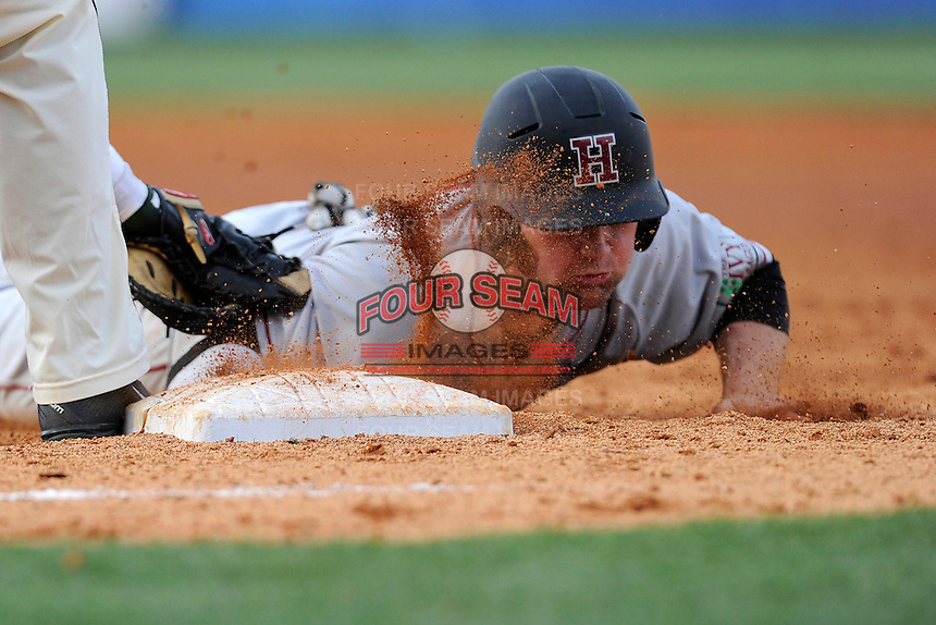Left fielder Jack Colton (9) of the Harvard Crimson gets a face full of dirt as he escapes a pickoff  in a game against the Michigan State Spartans on Saturday, March 15, 2014, at Fluor Field at the West End in Greenville, South Carolina. The first baseman is Ryan Krill (22). Michigan State won, 4-0. (Tom Priddy/Four Seam Images)