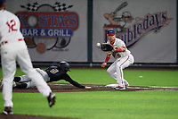 Auburn Doubledays first baseman Anthony Peroni (5) waits for a pickoff attempt throw from pitcher Rafael Gomez (12) as Victor Ngoepe (6) dives back to the bag during a NY-Penn League game against the West Virginia Black Bears on August 23, 2019 at Falcon Park in Auburn, New York.  West Virginia defeated Auburn 6-5, the second game of a doubleheader.  (Mike Janes/Four Seam Images)