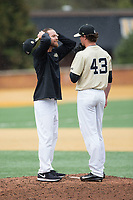 Wake Forest Demon Deacons assistant coach Matt Hobbs (31) has a meeting on the mound with relief pitcher Griffin Roberts (43) during the game against the Georgia Tech Yellow Jackets at David F. Couch Ballpark on March 26, 2017 in  Winston-Salem, North Carolina.  The Demon Deacons defeated the Yellow Jackets 8-4.  (Brian Westerholt/Four Seam Images)