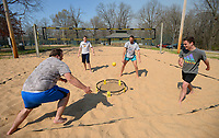 Friends Justus Bobo (from left), Gabe Skelton, Daniel Wenger and Carter Wade play a game of Spike Ball Friday, April 2, 2021, in the sand volleyball courts at Veterans Park in Fayetteville. The game shares qualities of volleyball as members of each team bounce the ball off of the net in the center. Visit nwaonline.com/210403Daily/ for today's photo gallery. <br /> (NWA Democrat-Gazette/Andy Shupe)
