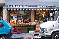 A grocery store with fruits and vegetables displayed on the pavement. Cars parked in front. Montevideo, Uruguay, South America
