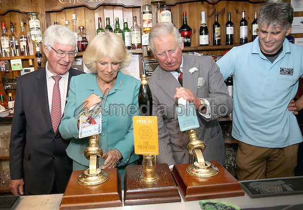 07 July 2015 - Llanarmon yn Lal, Wales - Camilla, Duchess of Cornwall pours a pint of 'Trickey Whu' while the Prince Charles, Prince of Wales pours a pint of 'Prince of Pales' during a visit to the Community-run Raven Inn Pub in Llanarmon yn Lal, Wales. Photo Credit: Alpha Press/AdMedia