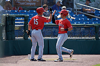 Batavia Muckdogs third baseman Denis Karas (9) is congratulated by Matt Brooks (15) on his way back to the dugout during a game against the Auburn Doubledays on June 17, 2018 at Falcon Park in Auburn, New York.  Auburn defeated Batavia 10-6.  (Mike Janes/Four Seam Images)