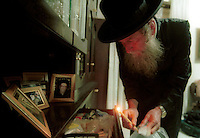Helped with a candle and a feather, as part of the Jewish tradition, an Orthodox Rabbi looks for the remains of leavened products in order to finish the cleaning of the house to make it kosher in preparation for the upcoming Pesach (Passover) holiday, March 26,2002 in Jerusalem. In this pre-festival ritual, practicing Jews remove all traces of leavened products from their homes in observance of Passover, which recounts the hasty exodus of the ancient Israelites from Egypt.. Photo by Quique Kierszenbaum