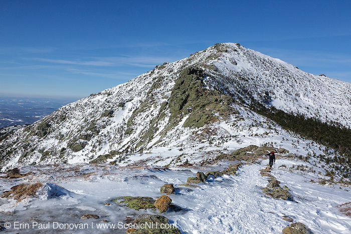 A lone hiker traveling south along the Appalachian Trail (Franconia Ridge Trail) in the New Hampshire White Mountains during the winter months. Mount Lincoln is in the background.
